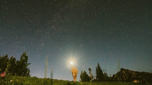 woman holds flashlight up to the night sky
