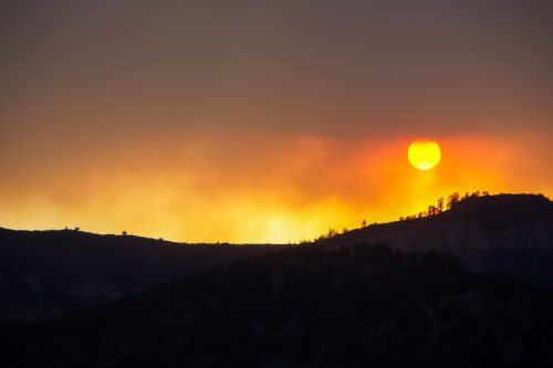 sun sets in sky filled with smoke from wildfires