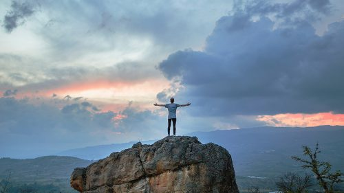 man with extended arms balances on rock formation as sun rises