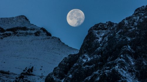 moon rises over mountains