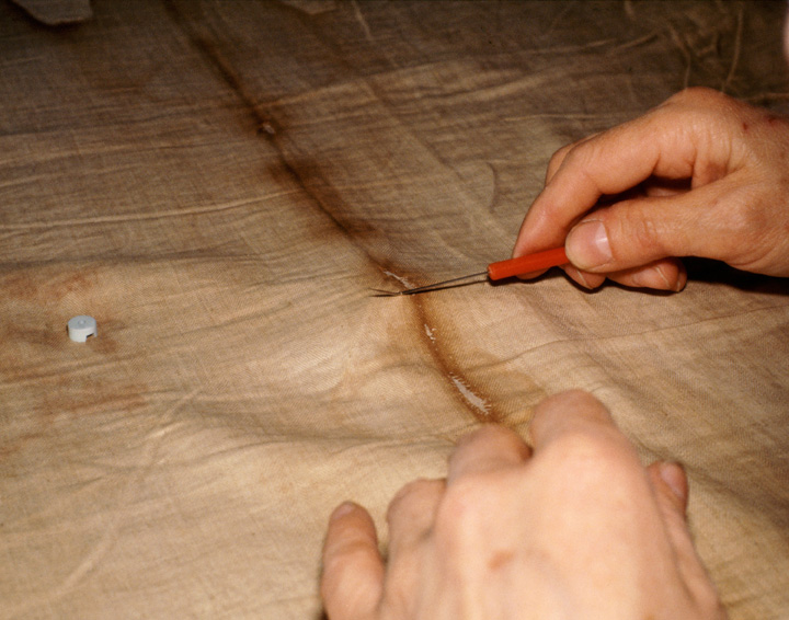 Nun's hands removing single thread from the Shroud of Turin.